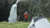 northern hemisphere : woman walks towards waterfall near campsite