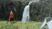 northern hemisphere : woman gets out of tent, walks towards waterfall