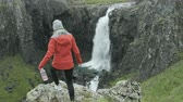 hidrasyon : woman walks towards cliff to check out view of waterfall in Iceland
