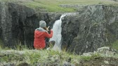 полушарие : woman taking photo of waterfall with her cell phone