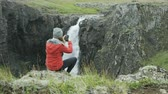 northern hemisphere : woman taking photo of waterfall with her cell phone