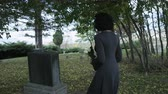 somber : Slow motion woman placing rose on top of grave stone in Cemetery Stock Footage