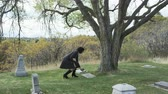 somber : slow motion of woman walking towards gravestone