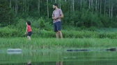 udržitelného : Camera looks through lake at father teaching young daughter to skip rocks, son enters frame and throws rocks Dostupné videozáznamy