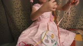 little : Cute little girl in a pink dress untangles colored ribbons.