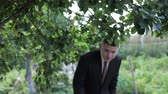 tkanička : Man in a suit passes under the branches of trees Dostupné videozáznamy