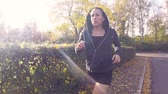 Slowmotion footage of a young fitness woman running in the autumn. The model is in the 20s and wearing a cardigan with hood.  Stock mozgókép