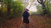 бегать трусцой : Active woman trail running in forest in the fall  autumn season. Exercising for a healthy body. Model is caucasian in the 20s.