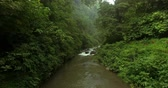 macera : Tropical jungle in Bali, Indonesia. Moving up a flowing river with green vegetaion on the sides.