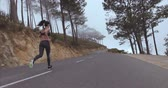 activities : Female runner running outdoor in morning. Fitness woman exercising on countryside road.