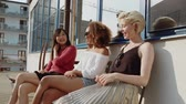 varanda : Group of three young women communicating while sitting in a balcony. Female friends sitting outdoor and gossiping. Stock Footage