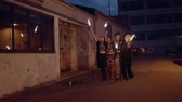 four people : Happy young people celebrating new years eve. Best friends walking on city street at night and celebrating  with sparklers outdoors. Stock Footage