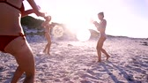 pistola : Footage of female friends playing with water guns on the beach. Group of three young women in bikini having water gun fight by the sea.