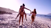 excitement : Slow motion video of young women friends enjoying piggy back ride on beach. Group of females having fun at the beach.