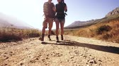 sujeira : Low angle tracking shot of couple hiking in nature. Man and woman walking on countryside dirt road.  Young people strolling on an extreme terrain.