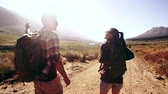 sujeira : Rear view footage of young man and woman talking and walking on a dirt road. Couple with backpack hiking on an extreme terrain. Stock Footage