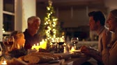 уютный : Happy family celebrating christmas together at home. Family sitting at dining table talking and having dinner together on Christmas eve. Стоковые видеозаписи