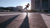 pontapé : Young woman doing martial arts practice in the city. Urban female athlete practicing high roundhouse kick on a sunny day outdoors. Stock Footage
