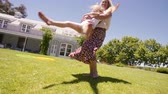 Happy mother with little girl having fun in backyard. Woman holding her daughter girl and spinning around.