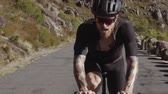 Slow motion video shot of a professional cyclist climbing uphill on road bike. Sportsman looking exhausted during steep climb on a bicycle.