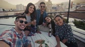 Multi-ethnic young people making a selfie at terrace party. Friends taking self portrait during party on rooftop.