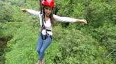 Young woman hanging over the dense rainforest , 3rd person on camera