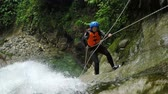 comprometido : Adult women rappelling huge waterfall in Andes rainforest, static camera , shot from above, model released footage