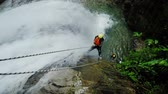 trough : Real time action shot of two tourist rappelling trough tall waterfall, static camera with sound, background voices