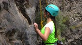 first : BANOS, ECUADOR - 30 MAY 2015: Young unidentified woman tries for the first time rock climbing at Basalt of Tungurahua competition in BANOS on MAY 30, 2015