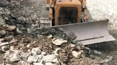 landslide : Front view of bulldozer moving rocks toward camera, high angle, static shot