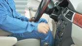 차 : A repairman dressed in a work uniform is in the car and checks the gearbox and dashboard