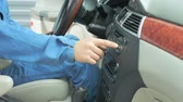 자동차 : A repairman dressed in a work uniform is in the car and checks the gearbox and dashboard