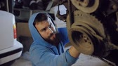 рычаг : The bearded car mechanic sits and from below screws the bolt into the body of the motor hanging on the chains. Стоковые видеозаписи