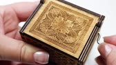 nota : Womans hands holding and playing a music box. Macro of the music box with intricate patterns and texture. Vídeos