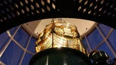 rehberlik : Close up of beautiful golden Fresnel lens inside Lighthouse, with gorgeous lights and shadows as lamp rotates. Stok Video
