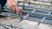 house builder : worker prepare metal rods with wire for concrete reinforcement