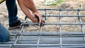 laje : worker prepare metal rods with wire for concrete reinforcement