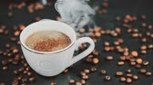 smell : Cup of hot drink with steam over black background. Slow motion.