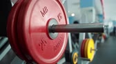 heavy : Male athlete preparing for intensive workout, loading heavy plates on barbell.