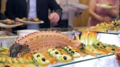 firmly : Restaurant guests select food from a buffet.