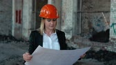crane : architect builder engineer builder of ruined building looking girl work plan for the construction site construction plan explains in helmet construction helmet girl looks architectural plan and construction plans to repair the area Stock Footage