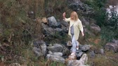 autumn : girl walking on the stones near the river 2