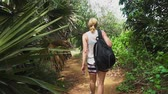 podróżnik : girl with a backpack travels through the rainforest. walking along the trail on the island