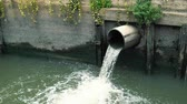 alcantarilla : Wastewater flows down from sewer pipe and pollutes water in river at downtown