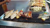 grillowanie : Night food market in Asia - fried calamari, chicken, pork, shrimp skewers on bbq grill Wideo