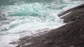 Sea foam falls on the rocky shore. Turquoise waves in the ocean Vídeos