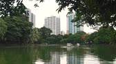 lumpini : Park with a large lake, green trees and palm trees in the downtown. A beautiful view of the skyscrapers from the city Park in summer day Stock Footage