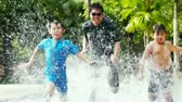 outdoors : Two Asian boys racing with their father in a pool.