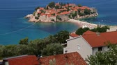 linha de costa : Sveti Stefan island tilting up. View blue sea water to horizon. Seacoast with old stone buildings. Sunny day blue sky clouds. Top view resort seashore. Sea coast line horizon.