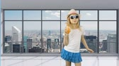 vela : Young girl walks in empty office and drinks orange juice. Behind panoramic windows can see cityscape and skyscrapers. Girl quenches her thirst with an orange cocktail. Good health.